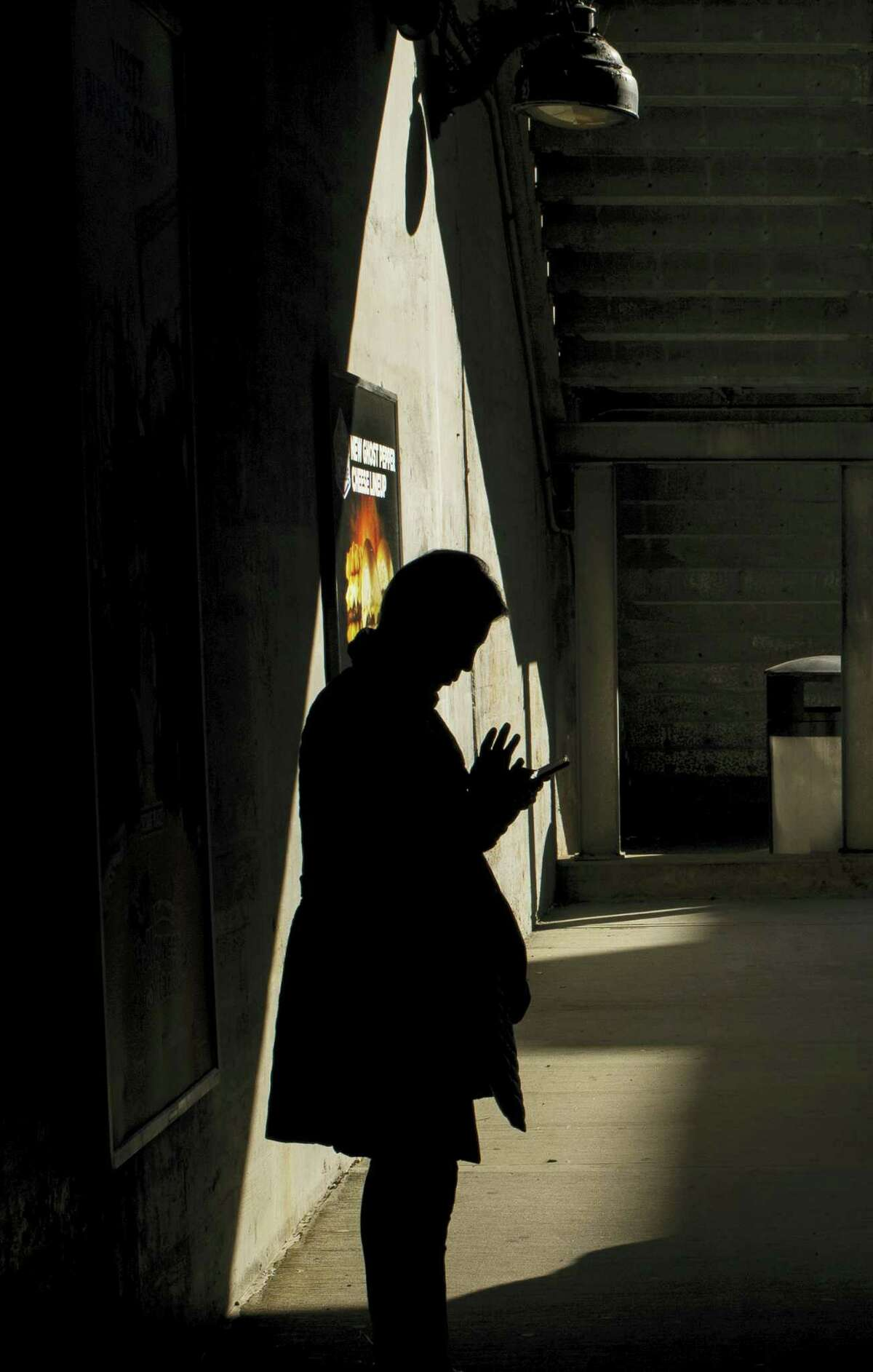 In this Oct. 12, 2016 photo, moments before boarding an arriving train to Manhattan, a morning commuter uses his smartphone on the platform of the Long Island Rail Road at the Bayside Station in the Queens borough of New York. TVs are so last century. News outlets are using Facebook Live, Snapchat, YouTube and other tools to offer live coverage of Election Day in ways not possible four years ago.