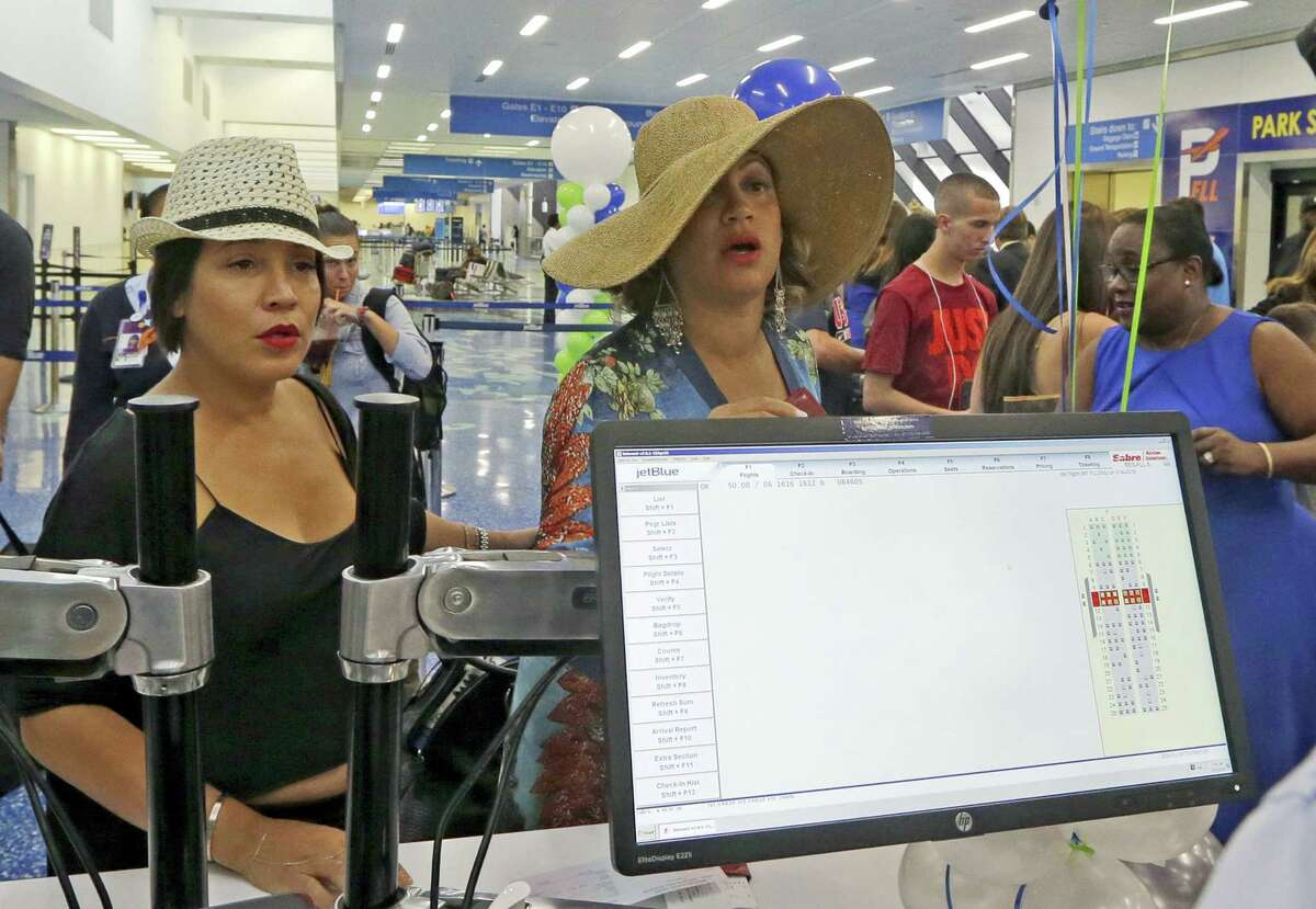 Michelle Sanchez-Boyce, left, and Erika Munro Kennerly, of New york, check in at the JetBlue counter to travel to Santa Clara, Cuba on Aug. 31, 2016, at the Fort Lauderdale-Hollywood International Airport in Fort Lauderdale, Fla. The first commercial flight between the United States and Cuba in more than a half century flew out of Fort Lauderdale for the central city of Santa Clara on Wednesday morning, re-establishing regular air service severed at the height of the Cold War.