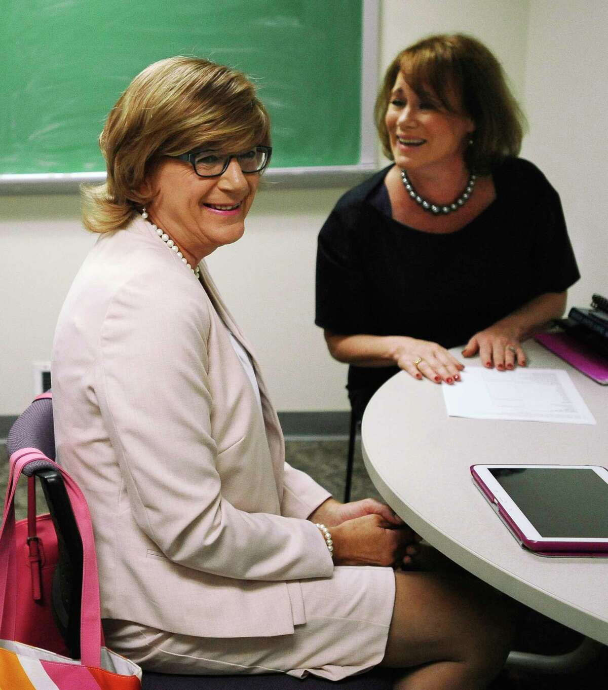In this July 22, 2015, photo, Brianne Roberts, left, smiles as she works on voice exercises with speech-language pathologist Jean McCarthy, right, at the University of Connecticut's Speech and Hearing Clinic in Storrs, Conn. Roberts is in a program at UConn that teaches transgender people how to sound more like the sex with which they identify.