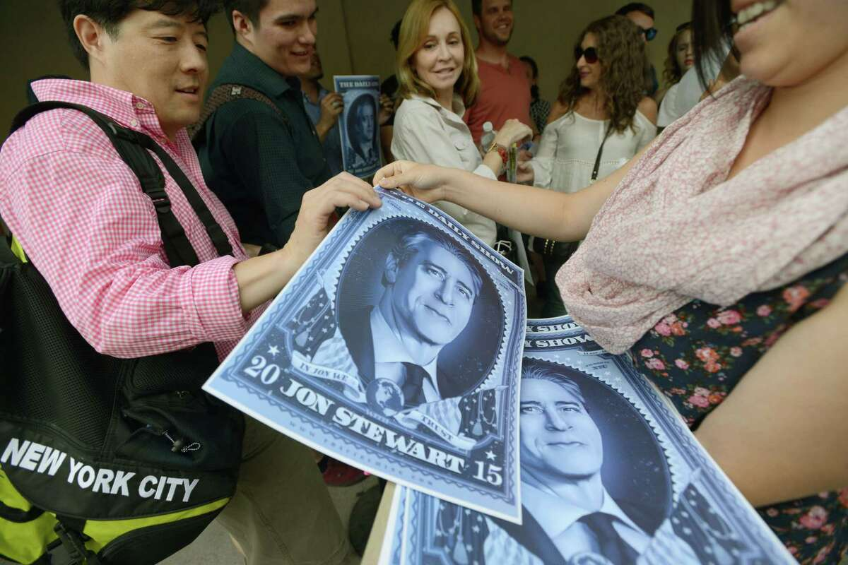 """People receive posters while in line for the taping of the final episode of """"The Daily Show"""" with Jon Stewart, Thursday, Aug. 6, 2015, in New York."""