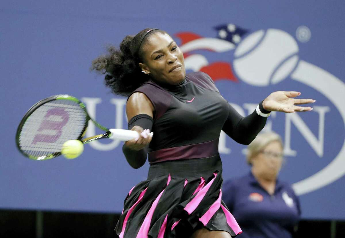 Serena Williams returns a shot from Ekaterina Makarova during the first round of the U.S. Open tennis tournament Tuesday. Williams won in straight sets.