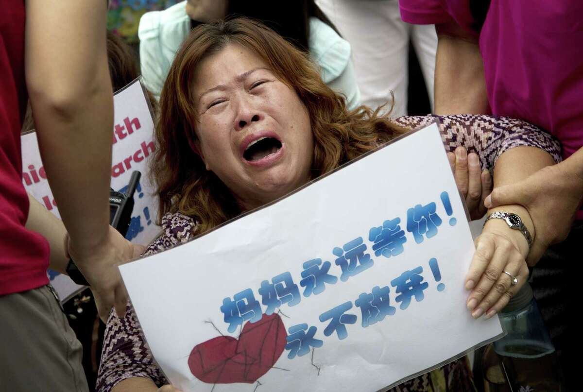 A relative of a passenger aboard Malaysia Airlines Flight 370, which went missing on March 8, 2014, is carried away by policemen as she and other family members kneel down and cry in front of the media during a protest near the Malaysian embassy in Beijing Friday, Aug. 7, 2015. Malaysia was intensely criticized early in the Flight 370 mystery for failing to quickly to disclose that its military radar had picked up an unidentified aircraft the night the Boeing 777 disappeared.