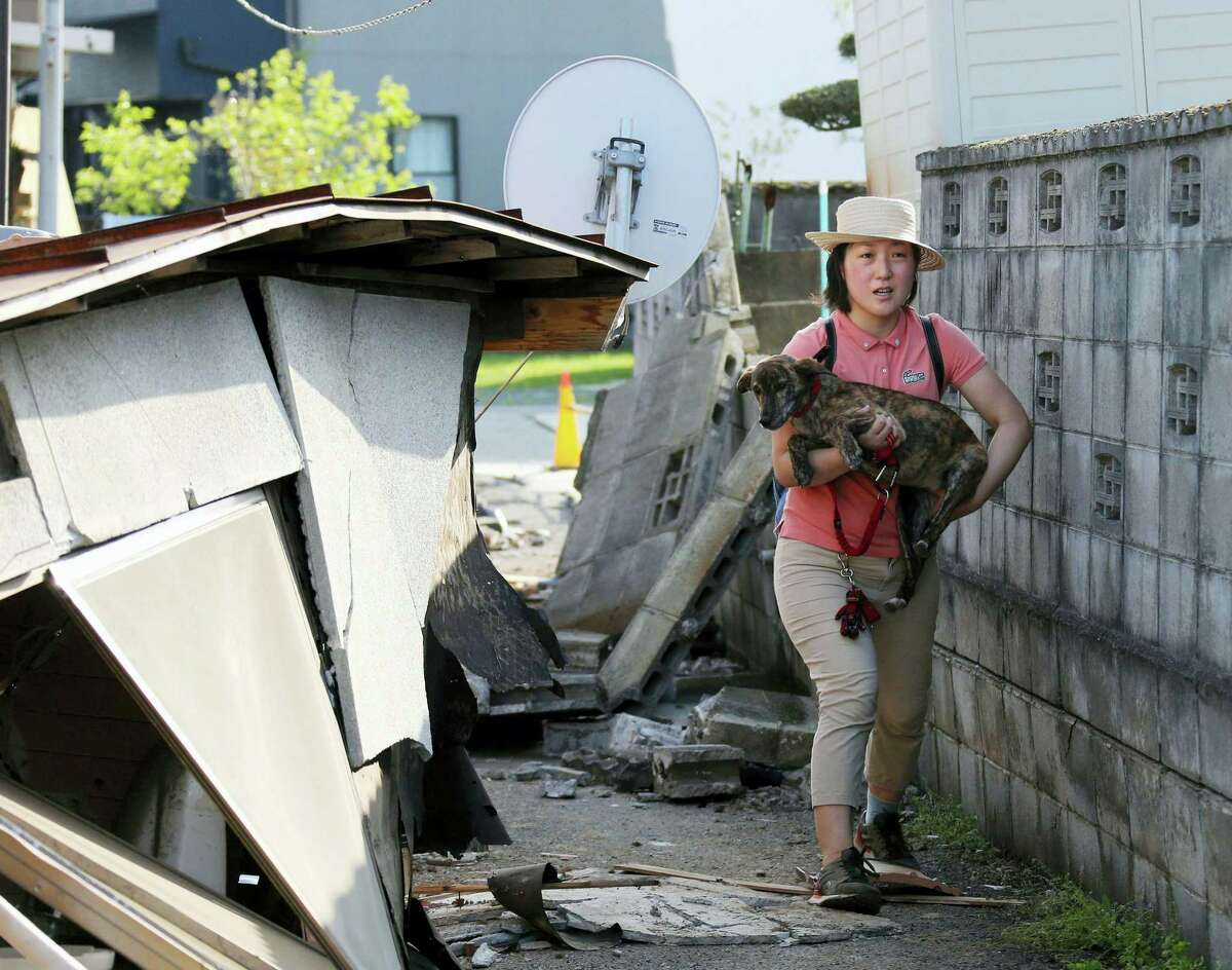 A resident carrying a dog walks by houses damaged by a first, magnitude-6.5 earthquake in Mashiki, Kumamoto prefecture, southern Japan, Friday, April 15, 2016. More than 100 aftershocks from Thursday night's magnitude-6.5 earthquake continued to rattle the region as businesses and residents got a fuller look at the widespread damage from the unusually strong quake, which also injured about 800 people. A second, 7.1 magnitude quake has now hit the island nation.