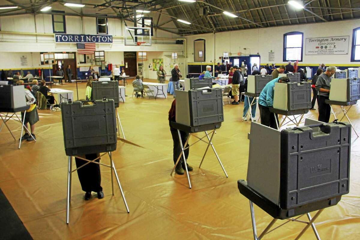 Esteban L. Hernandez - The Register Citizen Voters cast ballots inside the Torrington Armory Tuesday. The Armory is the polling place for the largest voting district in the city.
