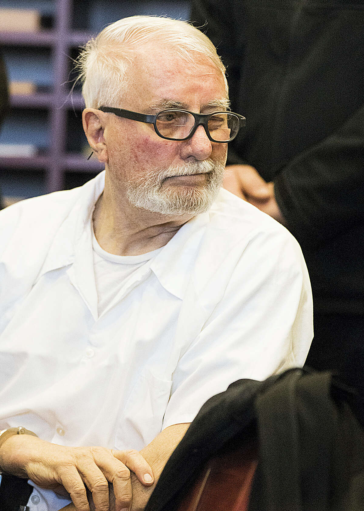 Jack McCullough winks at his stepdaughter Janey O'Connor behind him as he sits during a hearing in the DeKalb County Courthouse on Friday, April 15, 2016 in Sycamore, Ill. McCullough who a prosecutor says was wrongly convicted in the 1957 killing of an Illinois schoolgirl was released Friday shortly after a judge vacated his conviction, meaning that one of the oldest cold cases to be tried in U.S. history has officially gone cold again.