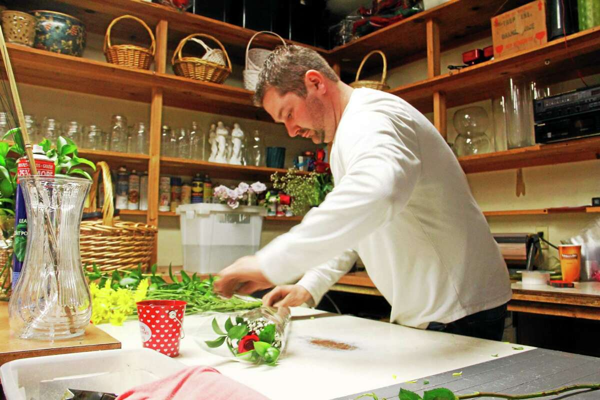 Kyle Curley, of the Flower Girl and Greenhouse Gifts, folds a rose bouquet in this Feb. 14, 2014, file photo in Torringon.