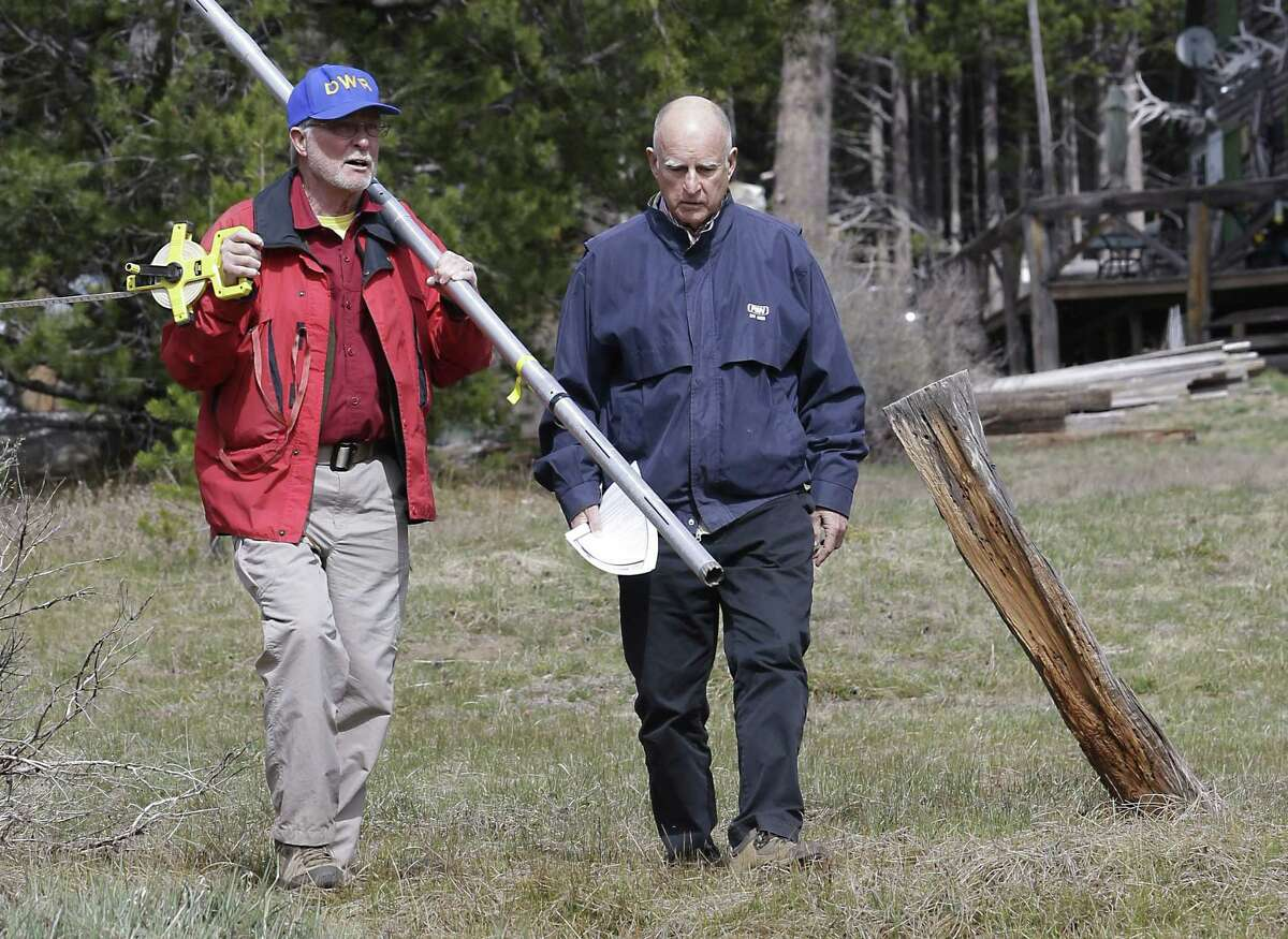 Frank Gehrke, left, chief of the California Cooperative Snow Surveys Program for the Department of Water Resources, and Gov. Jerry Brown walk across a dry meadow that is usually covered in several inches of snow as he conducts the snow survey, near Echo Summit, Calif., Wednesday, April 1, 2015. Gehrke said this was the first time since he has been conducting the survey that he found no snow at this location at this time of the year. Brown took the occasion to announce that he signed an executive order requiring the state water board to implement measures in cities and towns to cut water usage by 25 percent compared with 2013 levels.