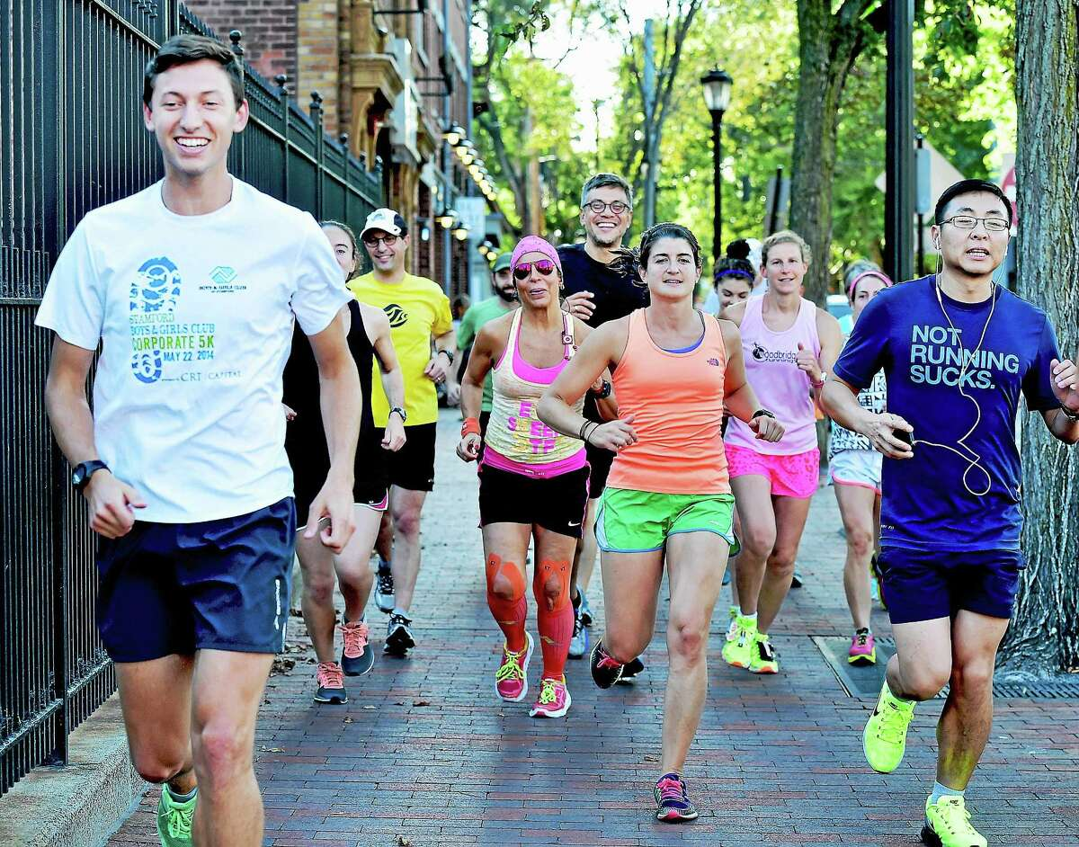 Area runners run on Elm Street Tuesday during the New Haven Road Race 20K training series in preparation for the annual Labor Day event.