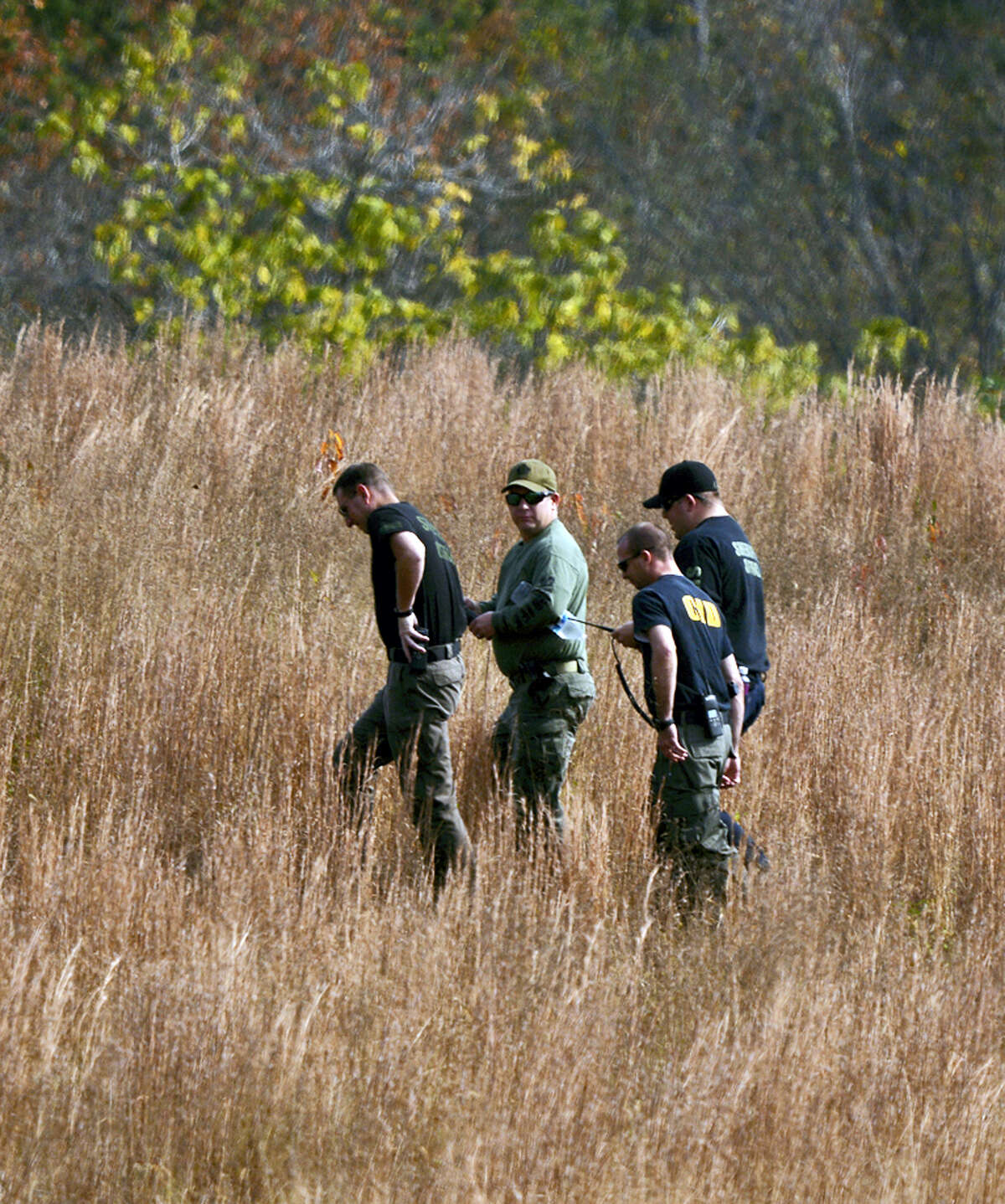 In this Nov. 3, 2016 photo, police search a field on property owned by Todd Kohlhepp where a missing woman was found chained up in a large storage container in Woodruff, S.C.