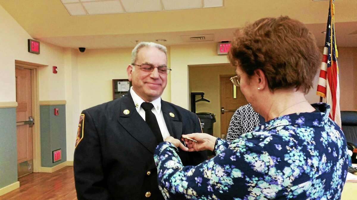 Fire Marshal Ed Bascetta is pinned by his wife at the Board of Public Safety meeting in Torrington Wednesday.