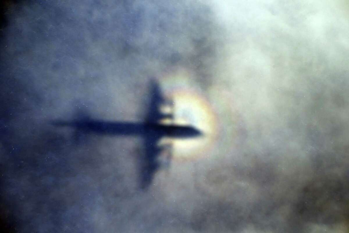In this March 31, 2014, photo, the shadow of a Royal New Zealand Air Force P3 Orion is seen on low level clouds while the aircraft searches for missing Malaysia Airlines Flight 370 in the southern Indian Ocean, near the coast of Western Australia. Malaysian Prime Minister Najib Razak announced on Thursday, Aug. 6, 2015, that a wing piece that washed up on Reunion Island last week is from the missing flight. However, French, U.S. and Australian authorities stopped short of full confirmation, frustrating relatives with mixed messages.