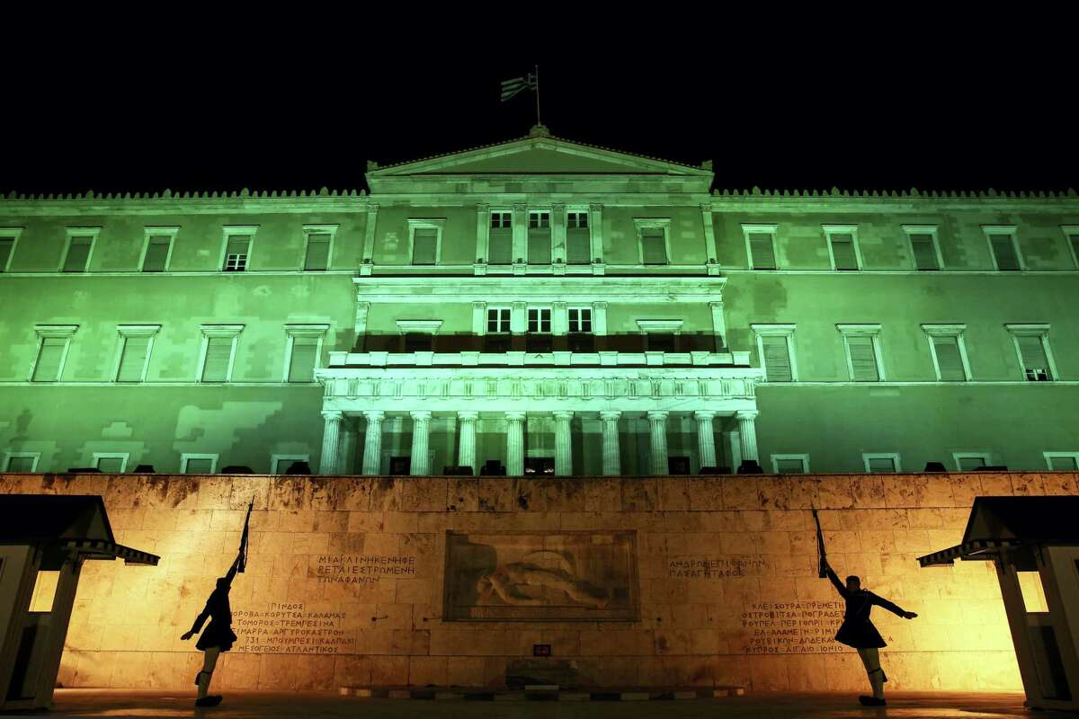 Presidential guards perform their ceremonial duties in front of the Greek parliament in Athens on Nov. 5, 2016. The parliament was illuminated in green light to celebrate the entry into the U.N. Paris Climate Change agreement.
