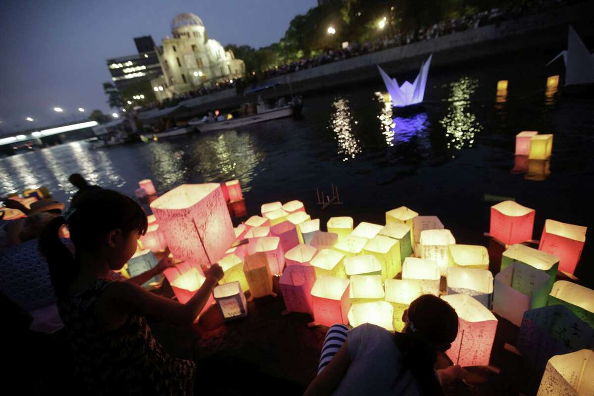 Children offer prayers after releasing paper lanterns on the Motoyasu River where hundreds of thousands of atomic bombing victims died with the backdrop of the Atomic Bomb Dome in Hiroshima, western Japan, Thursday, Aug. 6, 2015.