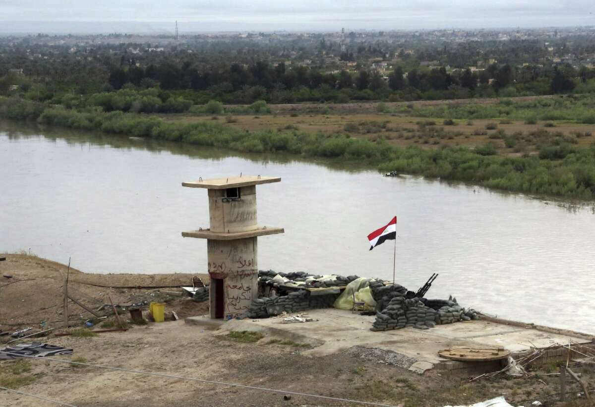 """An Iraqi flag waves over the Tigris River at a checkpoint in Tikrit, 80 miles (130 kilometers) north of Baghdad, Iraq, Wednesday, April 1, 2015. Iraqi security forces battled the last remaining pockets of Islamic State militants in Tikrit on Wednesday and were expected to gain full control of the city """"within the coming hours,"""" said Iraqi Interior Minister Mohammed Salem al-Ghabban. (AP Photo/Khalid Mohammed)"""