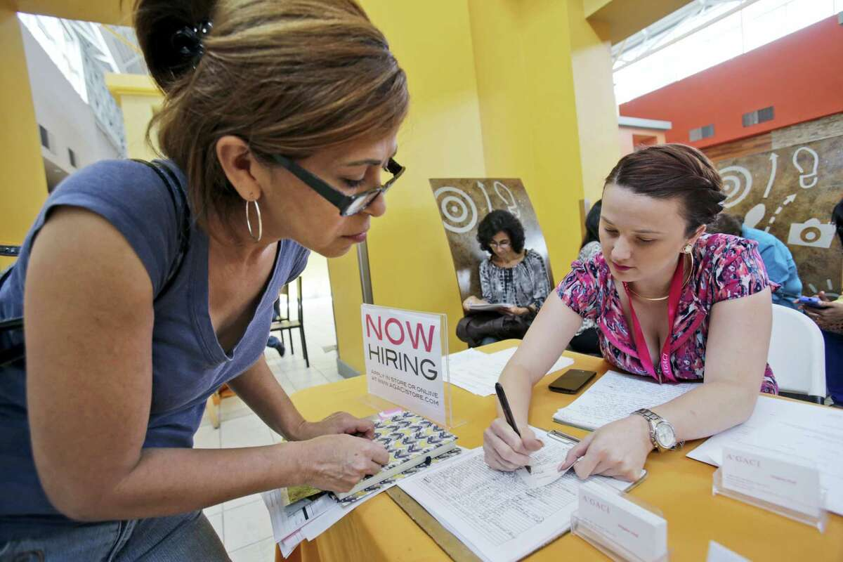 FILE - In this Oct. 6, 2015 photo, A'GACI clothing store hiring manager Marcie Lowe, right, gives her card to job applicant Xionara Garcia, left, of Miami, during a job fair at Dolphin Mall in Miami. Weekly applications for jobless benefits fell 13,000 to a seasonally adjusted 253,000, the Labor Department said Thursday, April 14, 2016. The four-week average, a less-volatile figure, dipped 1,500 to 265,000. The number of people collecting benefits declined 4.9 percent to 2.17 million. (AP Photo/Wilfredo Lee, File)