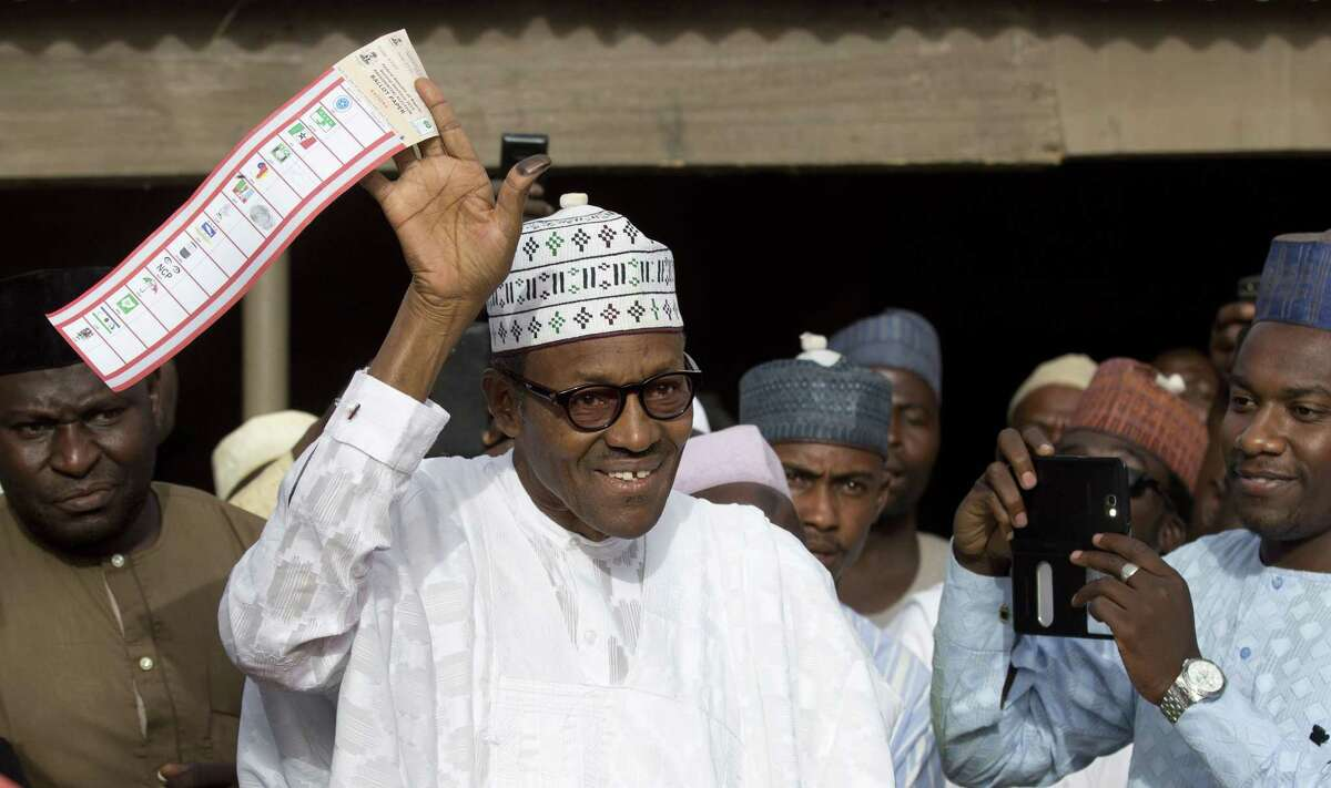 FILE - In this Saturday, March 28, 2015 file photo, opposition candidate Gen. Muhammadu Buhari holds his ballot paper in the air before casting his vote in his home town of Daura, northern Nigeria. On Tuesday, March 31, 2015 Nigeria's aviation minister said President Goodluck Jonathan had called challenger Muhammadu Buhari to concede and congratulate him on his electoral victory, paving the way for a peaceful transfer of power in Africa's richest and most populous nation. (AP Photo/Ben Curtis, File)