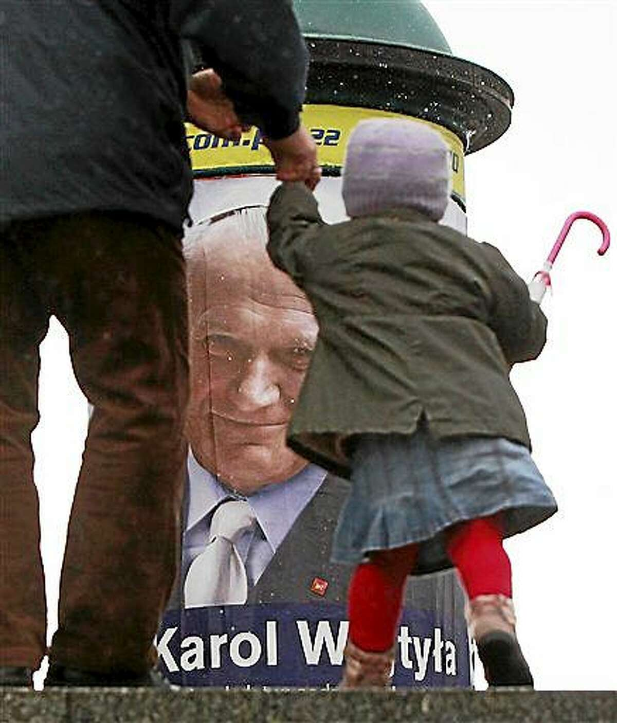 A pedestrian leads a child by a poster in Warsaw marking 10 years since the death of Polish-born Pope John Paul II. The poster encourages people to make their daily decisions in accordance with his teachings. John Paul will be gone a decade on Thursday. To attract attention to the poster, the pope, born as Karol Wojtyla, appears as a lay candidate in Poland's May 10 presidential elections.