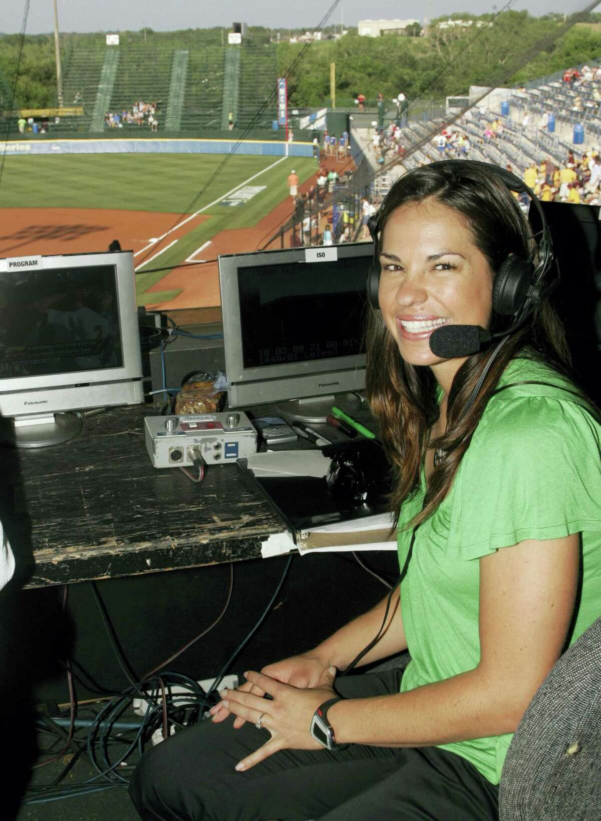 Jessica Mendoza poses for a photo in the ESPN broadcast booth at the Women's College World Series.