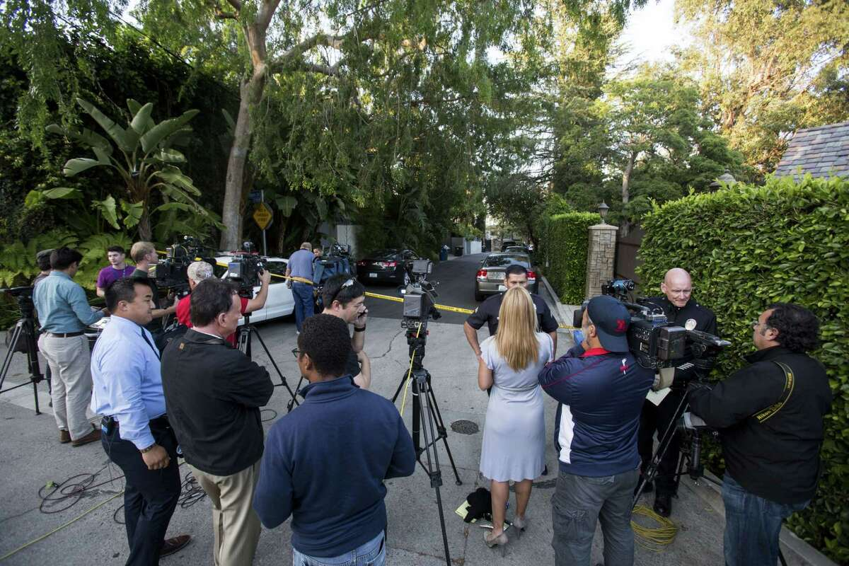 Members of the media wait outside a home in the Hollywood Hills area of Los Angeles on March 31, 2015. Police say a man was found dead at the home of Andrew Getty, heir to Getty oil fortune.
