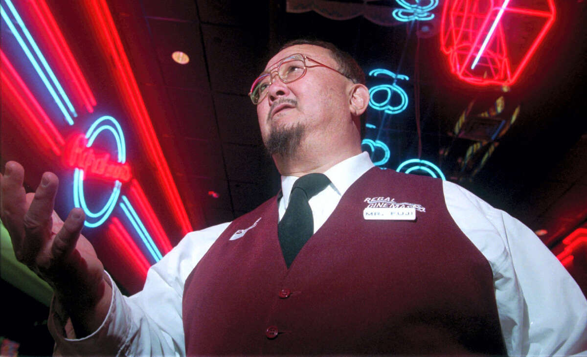 """In this April 2, 1999 photo, Harry Fujiwara, a former wrestler known as """"Mr. Fuji,"""" appears at a movie theater where he worked part time as an usher in Knoxville, Tenn. World Wrestling Entertainment said Sunday, Aug. 28, 2016 the former star wrestler and manager Fujiwara has died."""