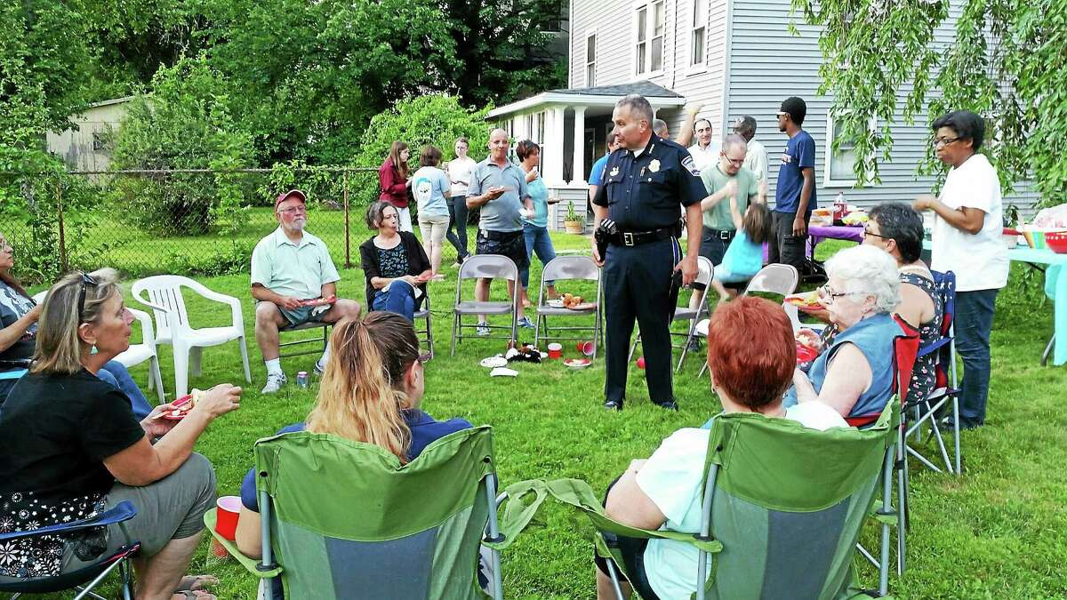 Police Chief Michael Maniago stands with members of community block watches Tuesday evening as part of National Night Out.