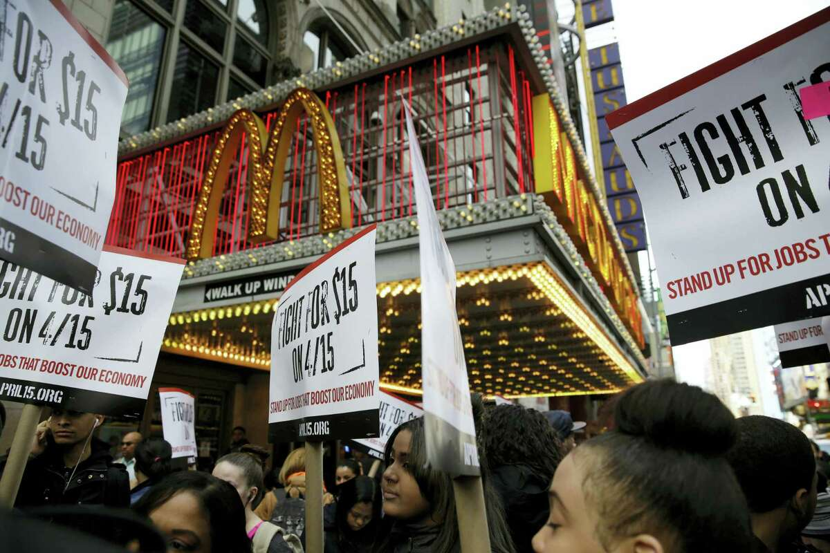 In this March 31, 2015 photo, people participate in a rally in front of a McDonald's restaurant in New York. Protesters calling for pay of $15 an hour and a union will be at McDonald's stores around the country and overseas on Thursday, April 14, 2016 as part of an ongoing push targeting the world's biggest hamburger chain.
