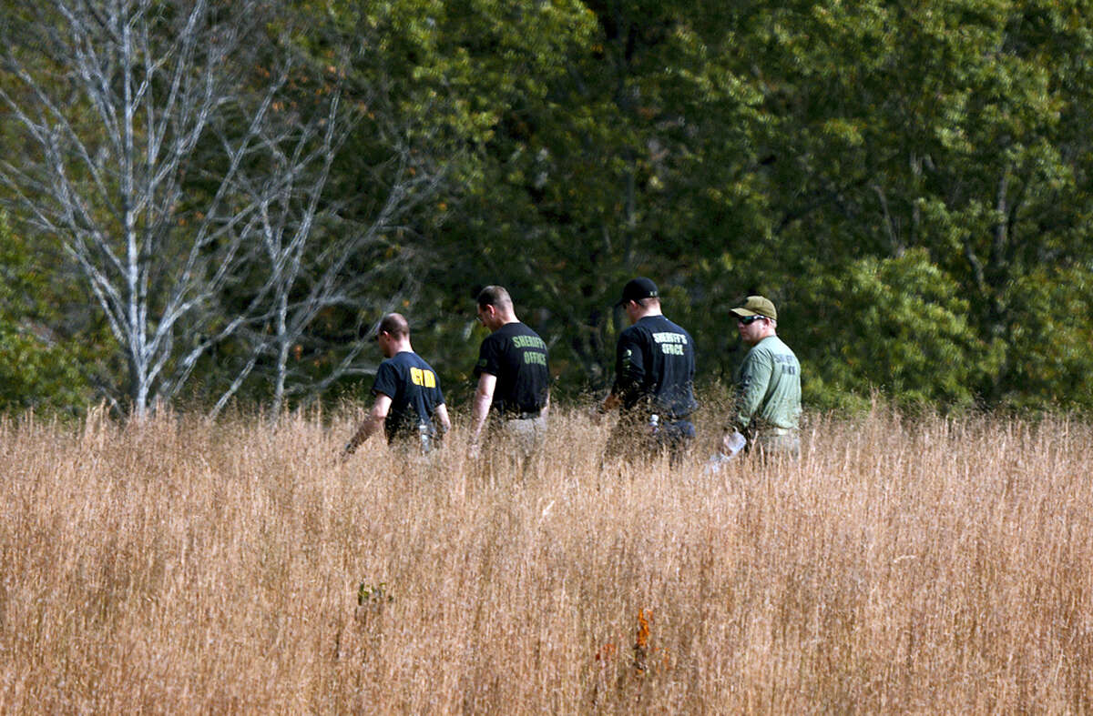 In this Thursday, Nov. 3, 2016, photo, police search a field on property owned by Todd Kohlhepp where a missing woman was found chained up in a large storage container in Woodruff, S.C.