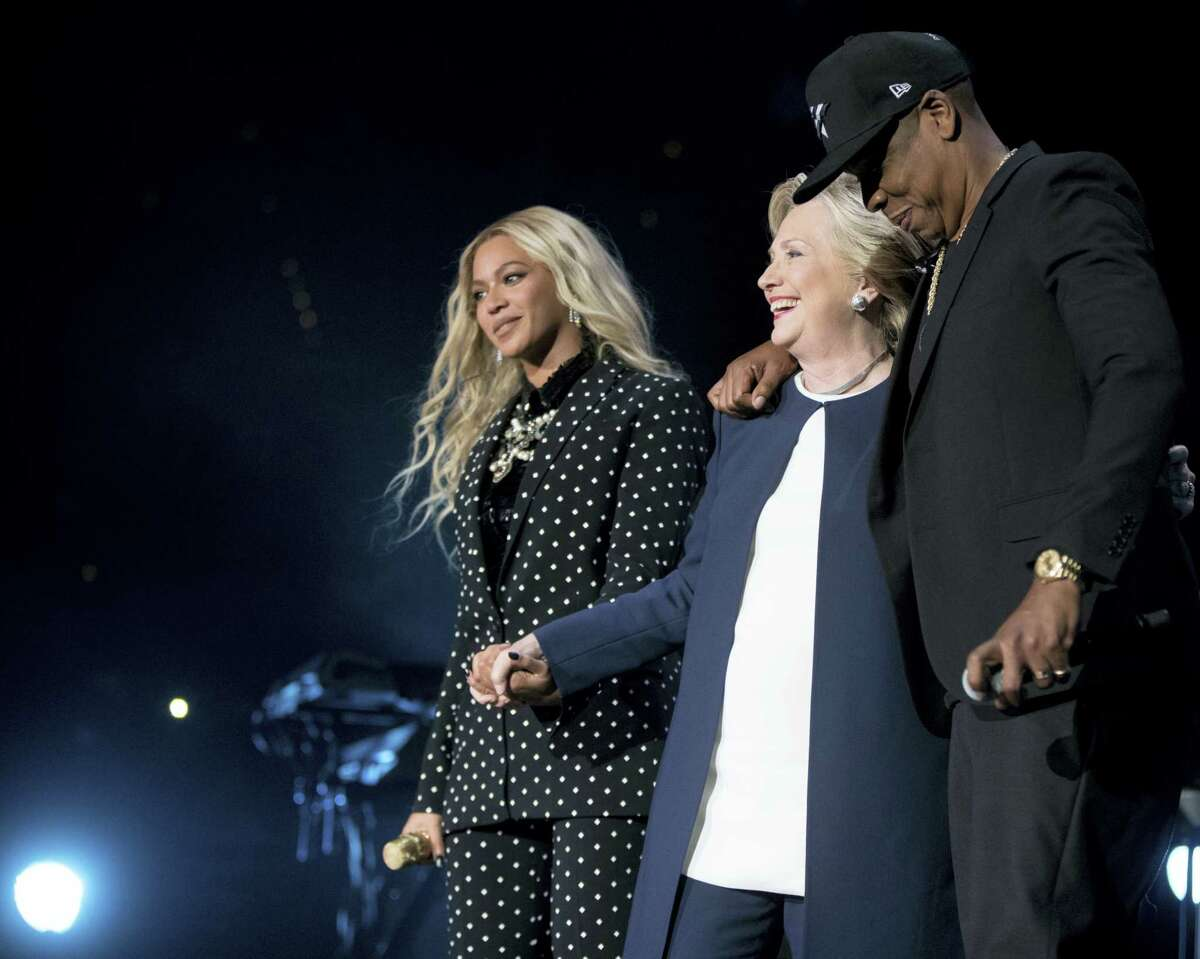 Democratic presidential candidate Hillary Clinton, center, is welcomed to the stage by artists Jay Z, right, and Beyonce, left, during a free concert at at the Wolstein Center in Cleveland, Friday, Nov. 4, 2016.