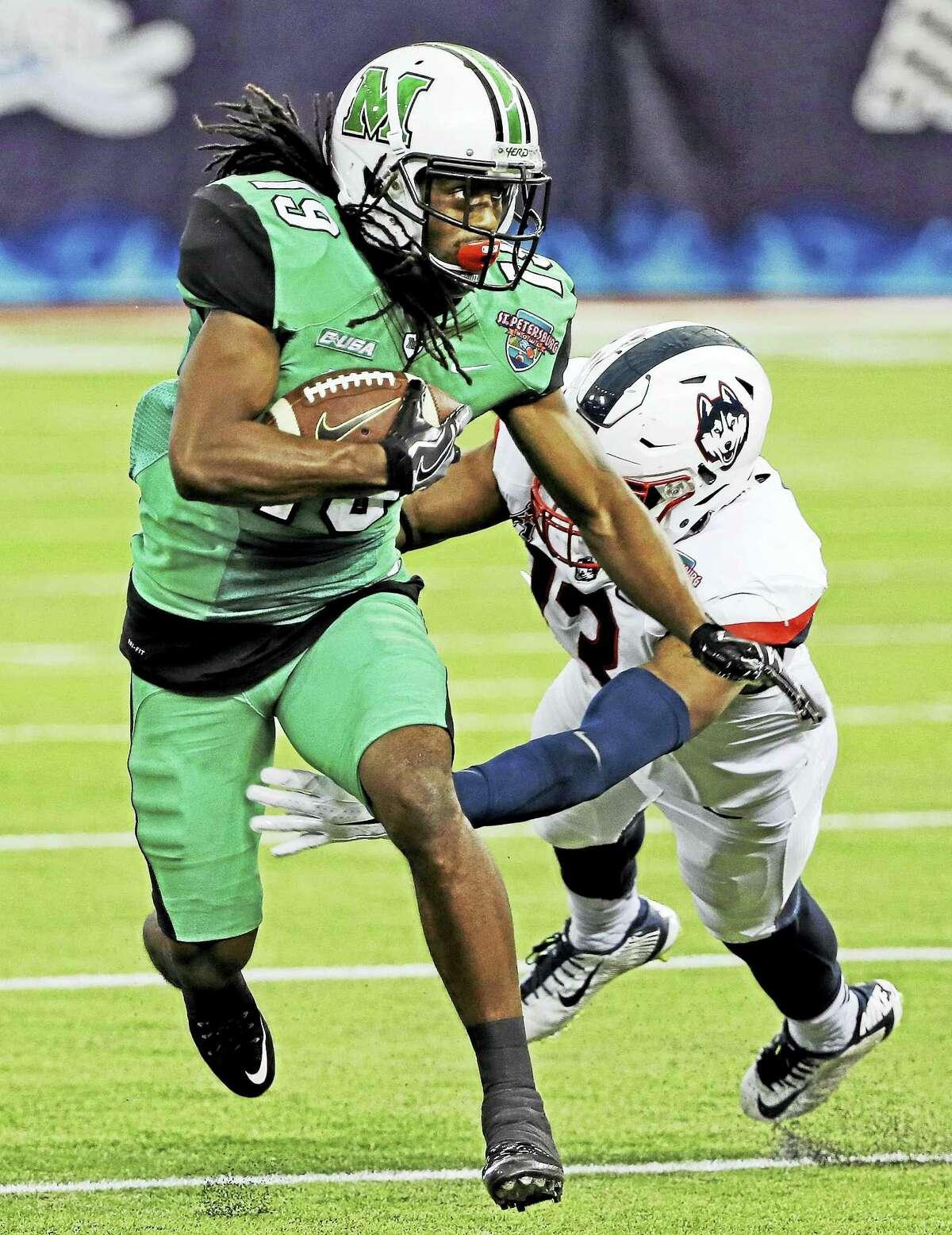 UConn linebacker Vontae Diggs tackles Marshall wide receiver Deandre Reaves during the St. Petersburg Bowl last December.