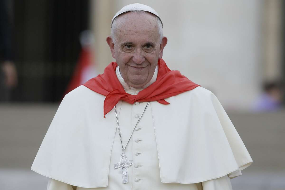 Pope Francis wears a red scarf as he leaves St. Peter's Square at the Vatican after an audience with Altar boys and girls on Aug. 4, 2015.