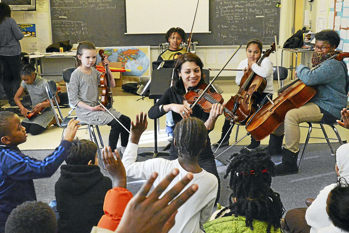 Violinist/teacher Yaira Matyakubova, backed by Music Haven students, plays for a group of refugee/immigrant children (foreground) in a visit to the after-school program at Fair Haven School.