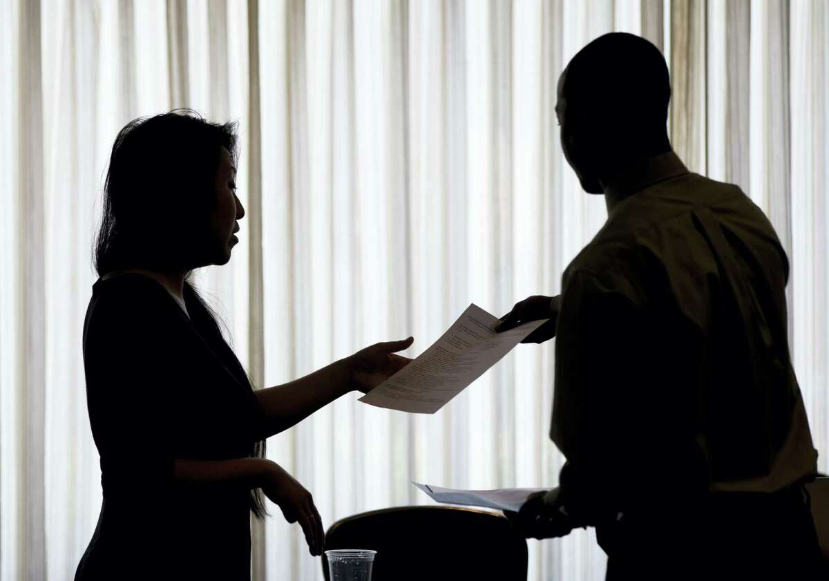 In this June 23, 2014, file photo, a recruiter, at left, takes the resume of an applicant during a job fair, in Philadelphia. On Thursday, Nov. 3, 2016, the Labor Department reports on the number of people who applied for unemployment benefits the week before.