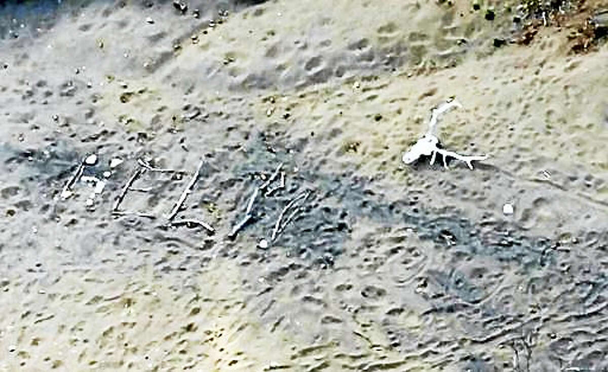 """This aerial photo taken Saturday, April 9, 2016, and provided by Arizona Department of Public Safety shows, a """"help"""" sign made by Ann Rodgers, 72, in the White Mountains of eastern Arizona. Rodgers got lost after her hybrid car ran out of gas and battery on March 31. She survived in the forest for nine days by drinking pond water and eating plants. Authorities came across her dog April 9, and a DPS flight crew spotted a """"help"""" signal made of sticks and rocks on the ground. Rodgers had left the area, but she was found on a reservation that's home to the White Mountain Apache Tribe after starting a signal fire."""