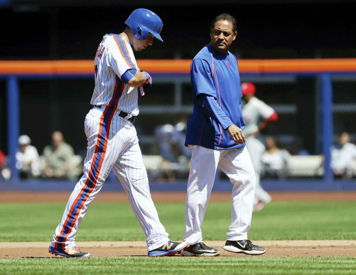 A trainer walks the Mets' Asdrubal Cabrera, left, off the field in the first inning on Sunday.