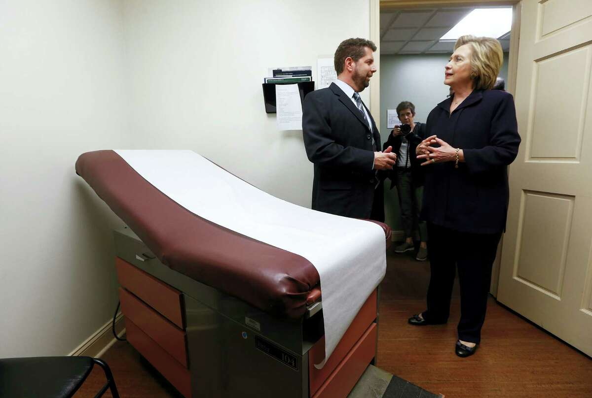 In this May 2, 2016 photo, Democratic presidential candidate Hillary Clinton listens to Dr. Christopher Beckett, CEO of Williamson Health and Wellness Center during a tour an exam room of the facility in Williamson, W.Va.