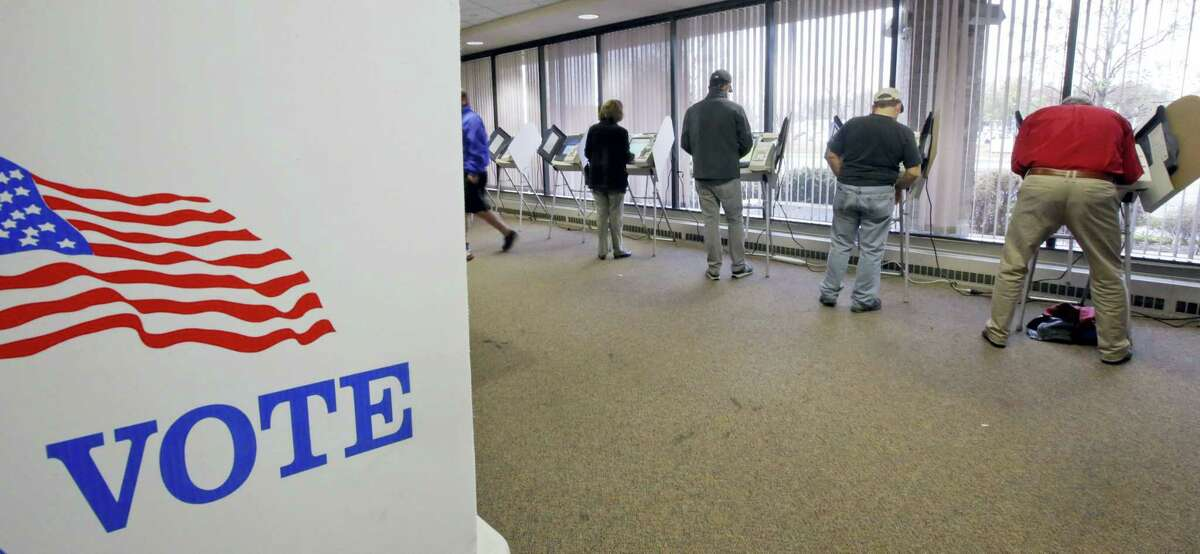 People vote during early voting for the 2016 General Election at the Salt Lake County Government Center on Tuesday in Salt Lake City.