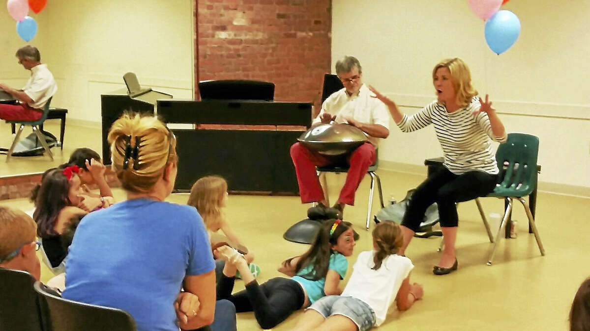 """N.F. Ambery photo Jeremy Driscoll plays the hang while Warner Theatre director of education Isabel Carrington tells children the story of """"The Devil with the Three Golden Hairs"""" during the Warner Theatre's third annual Family Arts Day."""