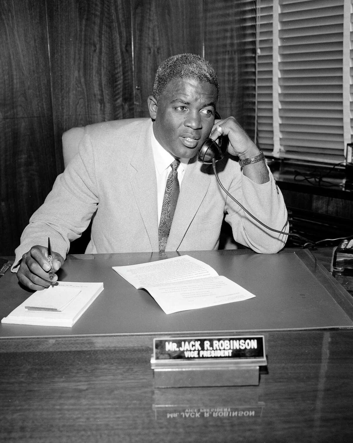 In this 1957 file photo retired baseball legend Jackie Robinson speaks on the phone at his desk in the offices of the Chock Full O' Nuts Company in New York.