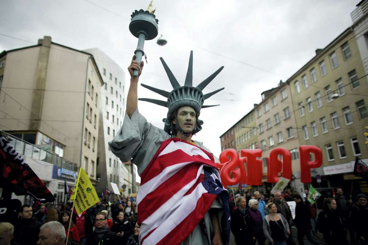 In this April 23, 2016 picture, a man walking on stilts and dressed like the Statue of Liberty attends a protest against the planned Transatlantic Trade and Investment Partnership, or TTIP, ahead of the visit of United States President Barack Obama in Hannover, Germany.