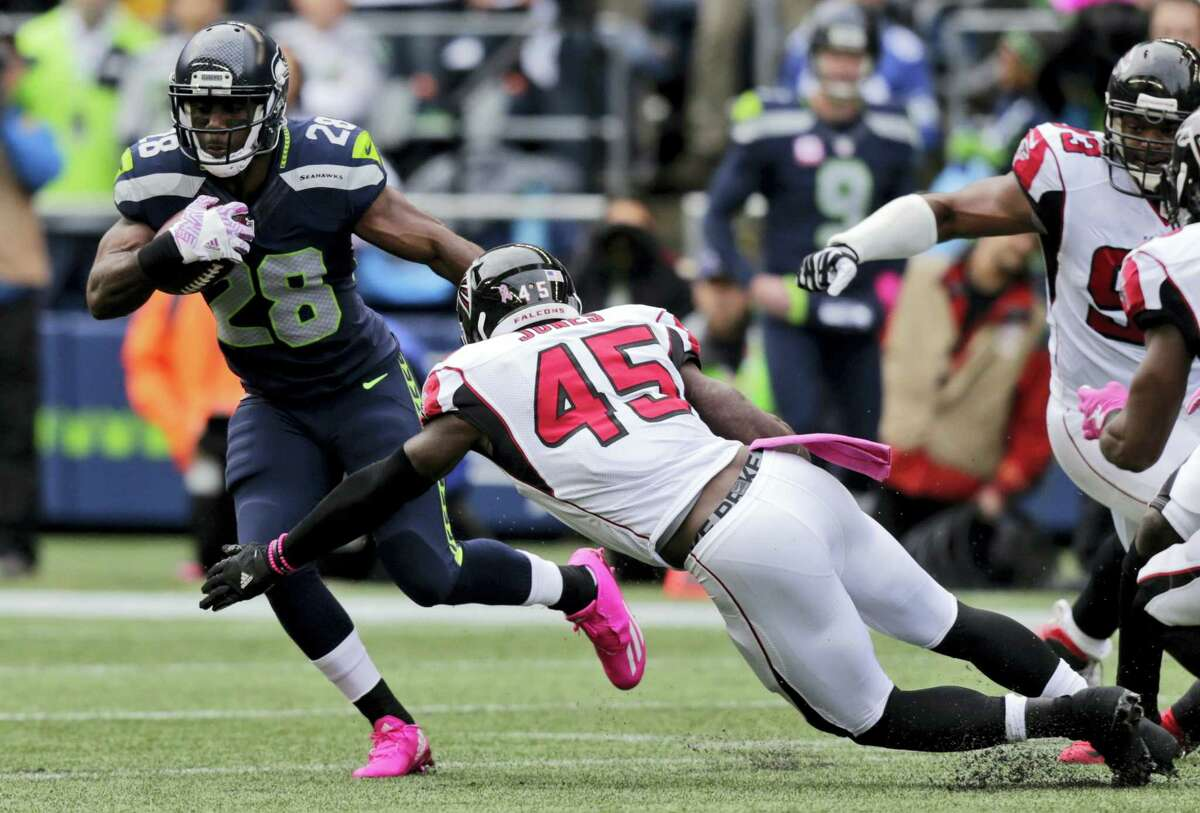 Running back C.J. Spiller (28), while playing for the Seahawks, is tackled by Atlanta Falcons strong middle linebacker Deion Jones earlier this season.