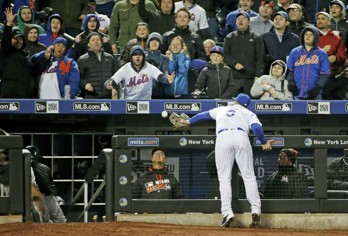 Marlins manager Don Mattingly, bottom center, watches from the dugout as Mets third baseman David Wright (5) tries to catch an eighth-inning foul ball on Tuesday. Wright couldn't make the play and the ball bounced into the stands.