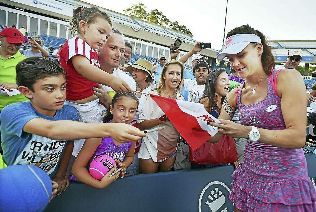Poland's Agnieszka Radwanska autographs a Polish flag after defeating Ukraine's Elina Svitolina in the championship match at the Connecticut Open on Saturday.