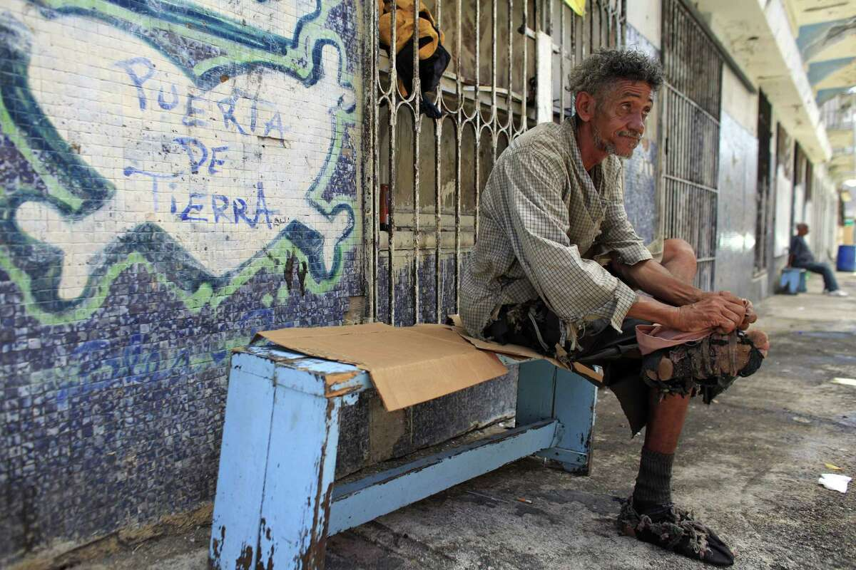 A homeless man improvises his shoes with pieces of cloth in front of a closed down business in Puerta de Tierra in the outskirts of Old San Juan, Puerto Rico.