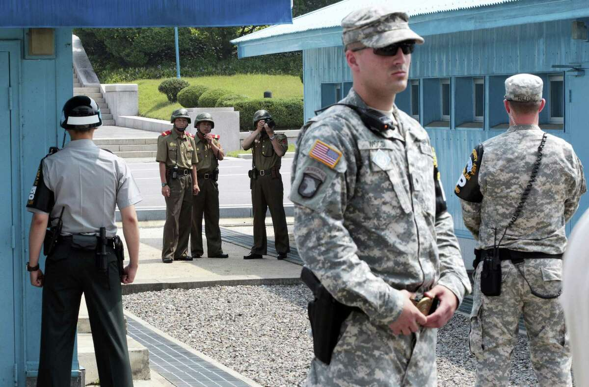 In this July 27, 2014, file photo, North Korean army soldiers watch the south side while a South Korean and United States Army soldiers stand guard at the border villages of Panmunjom in Paju, South Korea. North Korea has threatened on Saturday, Aug. 27, 2016, to aim fire at the lighting equipment used by American and South Korean troops at a truce village inside the Demilitarized Zone that divides the two Korea.