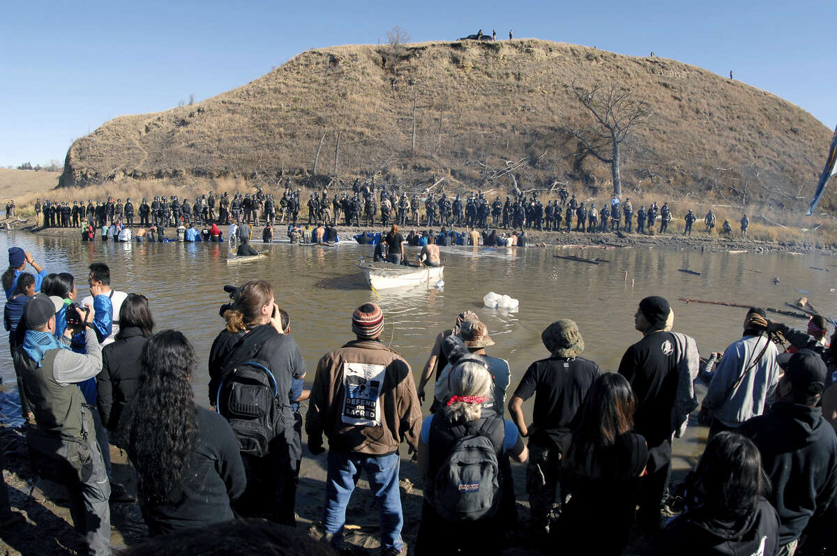 A Dakota Access Pipeline protesters stand in the foreground and in the waist-deep water of the Cantapeta Creek, northeast of the Oceti Sakowin Camp, near Cannon Ball, N.D., Wednesday, Nov. 2, 2016. Officers in riot gear clashed again Wednesday with protesters near the Dakota Access pipeline, hitting dozens with pepper spray as they waded through waist-deep water in an attempt to reach property owned by the pipeline's developer.