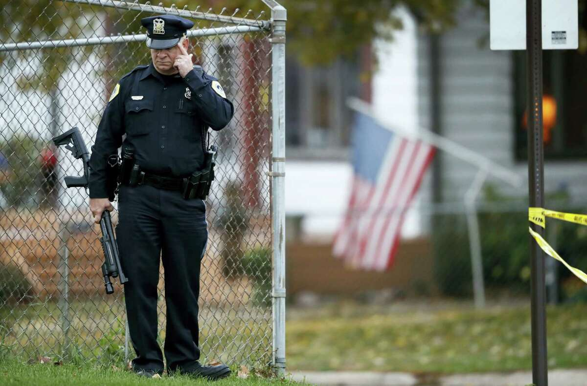 A Des Moines police officer stands near the scene of a shooting, Wednesday, Nov. 2, 2016, in Des Moines, Iowa. Authorities apprehended a man Wednesday suspected in the early morning killings of two Des Moines area police officers who were shot to death while sitting in their patrol cars in what authorities described as separate ambush-style attacks.