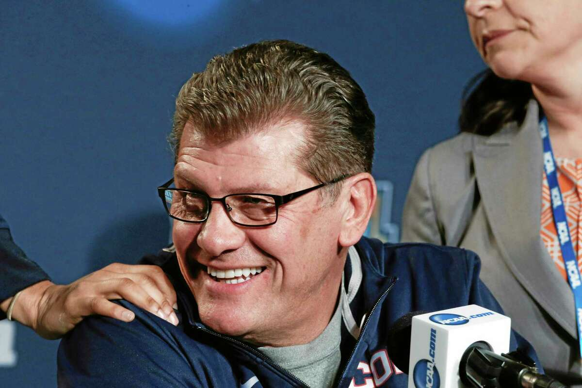 Connecticut head coach Geno Auriemma gets a pat on the shoulder as his players leave a news conference at the NCAA women's Final Four college basketball tournament Monday, April 7, 2014, in Nashville, Tenn. Connecticut is scheduled to face Notre Dame in the championship game Tuesday. (AP Photo/John Bazemore)
