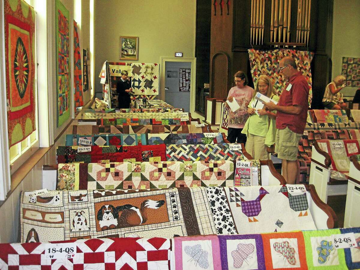 Visitors view quilts draped over church pews.