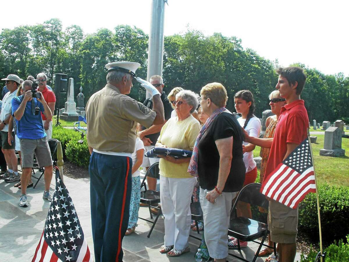 Barbara Bongiolatti hands over the flag that will be flown in honor of her late husband, Private 1st Class U.S. Army veteran Emilio Bongiolatti, at the All Wars Memorial in Bantam until Sept. 5.