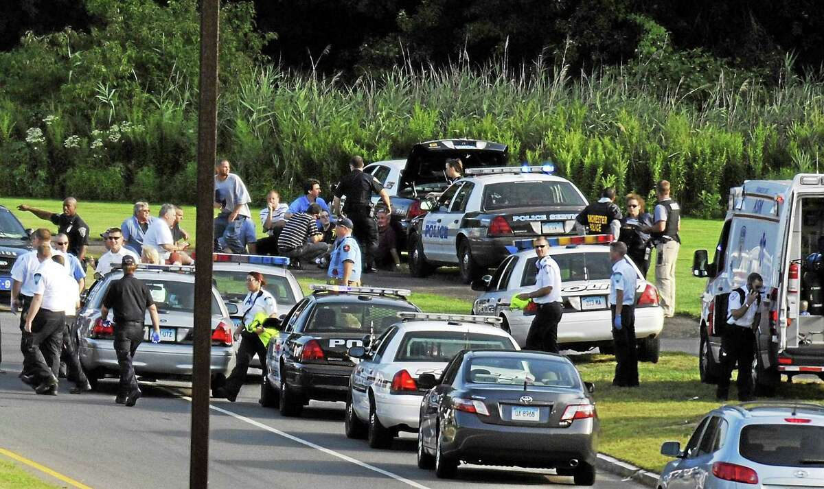 Employees of Hartford Distributors sit behind a police car after evacuating the building in Manchester, Conn. on Aug. 3, 2010. Ormar Thornton, a driver for Hartford Distributors, killed eight people, plus himself at the beer distribution company that Tuesday morning.